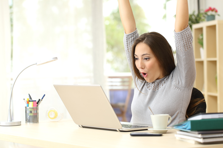 woman celebrating in front of computer